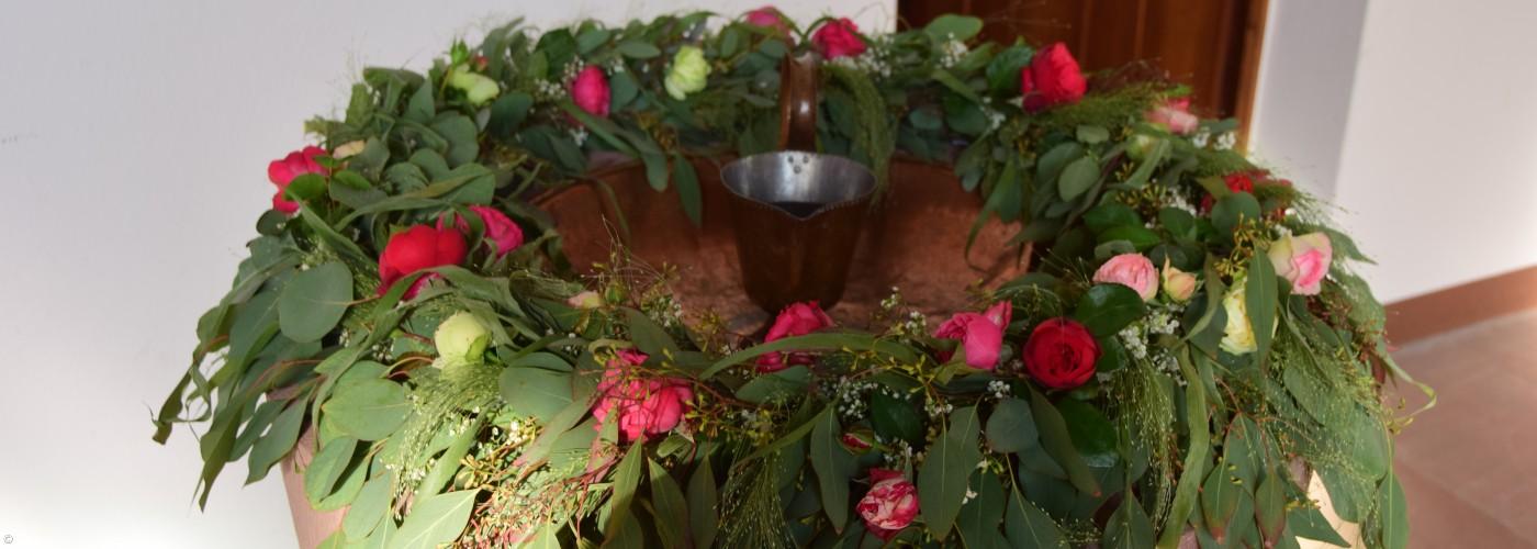 Blumenschmuck auf Taufstein